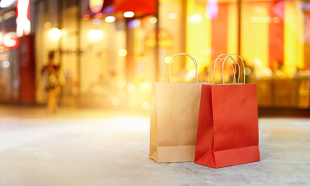 Red and brown shopping bags on floor front the mall store at night, business, retail, banner and sign concept