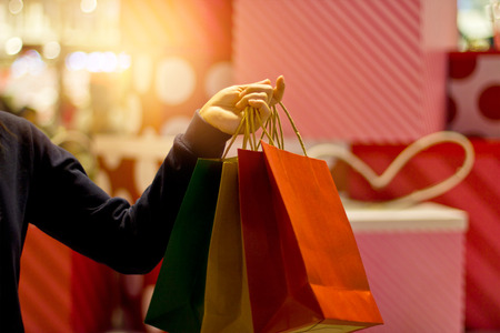 Christmas shopping - shopping bags in hand on the mall departstore background, soft focus