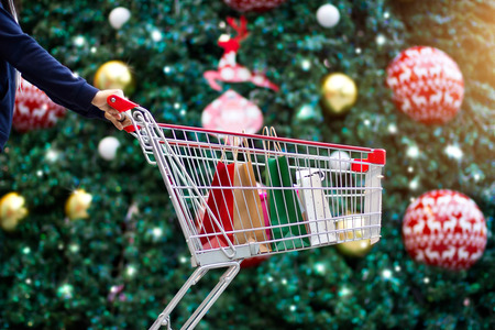 Christmas shopping - woman shopper with bags in shopping cart on holidays ornament and christmas tree on street background