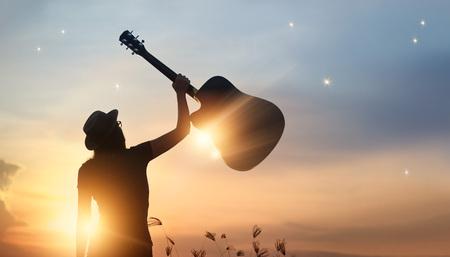 Muzyk trzyma gitarę w ręce sylwetka na zmierzch natury tle