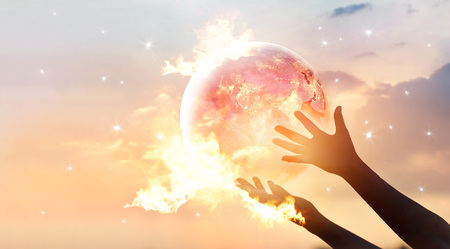 Save the world energy campaign. Planet earth with flame on human hands show energy consumption of humanity at night, Elements of this image furnished by NASA Archivio Fotografico