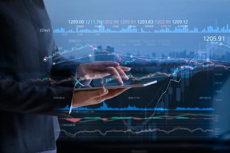 Ludzie biznesu sprawdzający giełdę na tablecie i analizujący dane finansowe na ekranie z wykresem i wykresem świecowym na wirtualnym monitorze LED na tle miasta