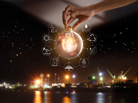 Hand holding light bulb in front of global show the world's consumption with icons energy sources for renewable, sustainable development. Ecology concept. Elements of this image furnished by NASA. Stockfoto