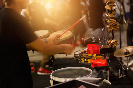 Man playing musical percussion instrument on street background, soft focus Stock Photo