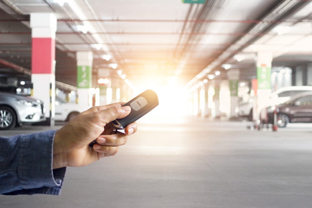 Hand of holding and push key remote control of car on underground parking background Standard-Bild