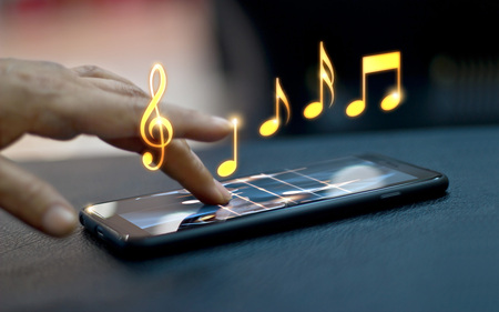 Abstract hand playing music notes on smartphone at night background, music concept