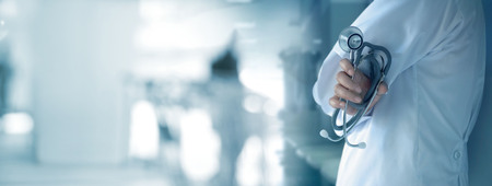 Doctor with stethoscope in hand on hospital background, medical and medicine concept
