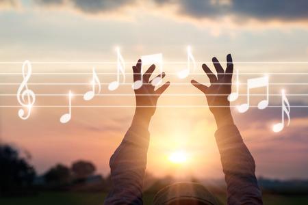 自然の背景、音楽の概念に音楽ノートに触れる抽象的な女性の手