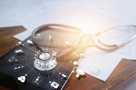 Stetoskop z ikoną medyczną na tablecie i tle drewniany stół