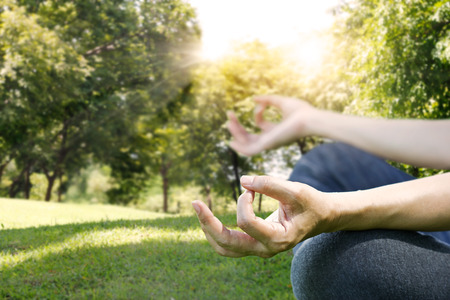 hands of woman meditating on a yoga pose on the park Standard-Bild