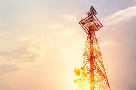 Abstracte telecommunicatie torenantenne en satellietschotel bij zonsondergang hemelachtergrond