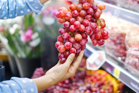 Woman choosing bunch fresh red grape to buy in supermarket Standard-Bild