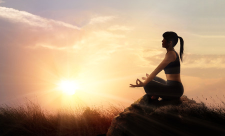 Woman meditating yoga at sunset mountains with nature. Outdoor sport exercise and relaxation concept