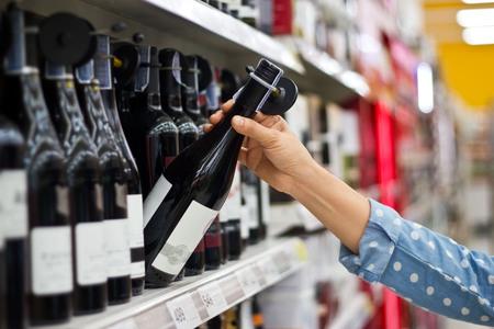 여자는 슈퍼마켓 배경에서 와인 한 병을 구입