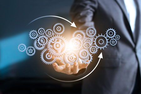 Business mechanism concept. Businessman holding with connected gears icons and business processes workflows on virtual screen.