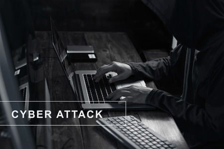Internet crime. Hacker using laptop and hack code password in the dark room. Cyber attack concept
