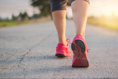 Close up sneaker of athlete woman runner feet on rural road while running exercise on sunset background