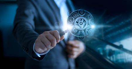 Businessman looking through a magnifying glass of gears to success. Teamwork concept Standard-Bild
