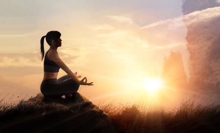 Woman practices meditating yoga at is an asana on a stone, sunset mountains background Standard-Bild