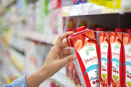 Woman hand choosing to buy strawberry juice on shelves in supermarket Standard-Bild