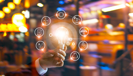 Hand holding light bulb in front of global show the world's consumption with icons energy sources for renewable, sustainable development. Ecology concept. Stockfoto