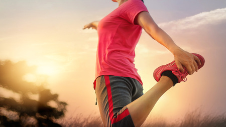 Young woman runner stretching legs before running at sunset rural trail. Stock Photo