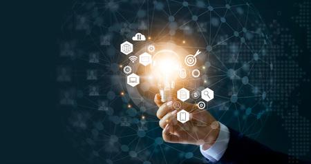 Geschäftsmann, der Glühlampe und neue Ideen des Geschäfts mit innovativer TechnologieNetzwerkverbindung hält. Geschäftsinnovationskonzept.