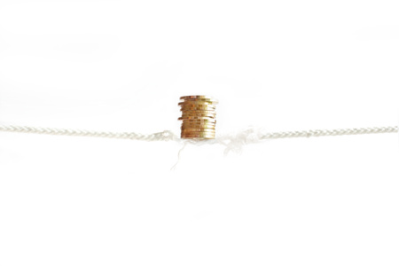 Row of golden coins is sustained balancing on nearly absent rope. Money,  business finance and investment concept 版權商用圖片