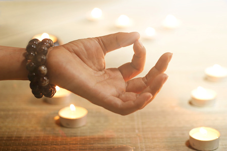 Woman hand yoga and meditation on candle warm glowing background Foto de archivo