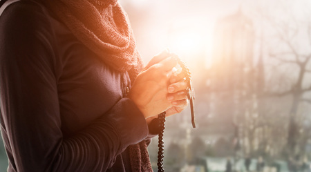 Christian Religion and hope concept. Woman hands praying with rosary and wooden cross. Bless god helping catholic on church background. Stockfoto