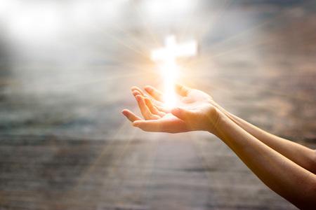 Femme avec croix blanche dans les mains priant pour la bénédiction de Dieu sur fond de lumière du soleil, concept de l'espoir Banque d'images