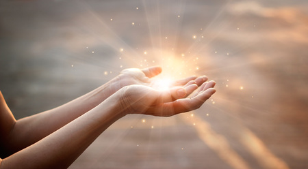 Woman hands praying for blessing from god on sunset background 写真素材