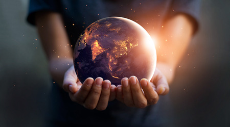 Earth at night was holding in human hands. Earth day. Energy saving concept Фото со стока - 99514666