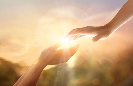 Gottes helfende Hand mit dem weißen Kreuz auf Sonnenunterganghintergrund. Gedenktag und Karfreitagskonzept