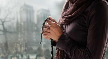 Woman praying with rosary and wooden cross on church background. Hope concept Stock Photo