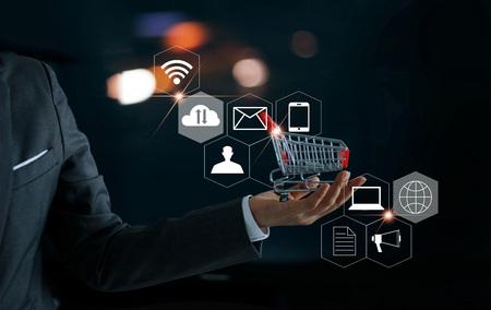 Zakenman met in de hand winkelwagentje en pictogrammen klant netwerkverbinding. Digitale marketing en online winkelen. Bedrijfs- en betalingsconcept