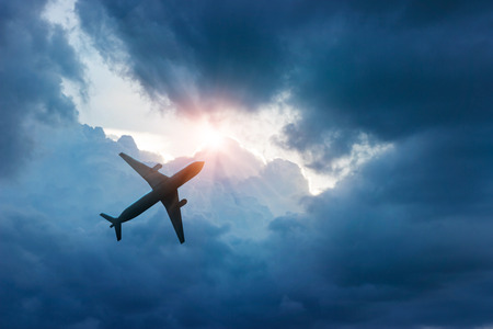 Airplane in the dark blue sky and cloud at sunrise Stock Photo