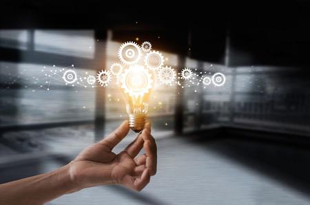 Mano que sostiene la bombilla y la rueda dentada adentro. Idea e imaginación. Creativo e inspirador. Icono de engranajes de innovación con conexión de red sobre fondo de textura de metal. Tecnología innovadora en ciencia y concepto industrial. Foto de archivo