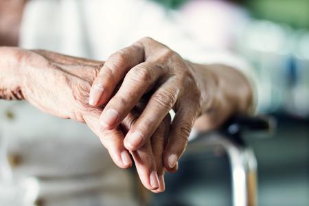 Schließen Sie die Hände der älteren älteren Patientin, die an Pakinsons Krankheitssymptom leidet. Konzept für psychische Gesundheit und Altenpflege