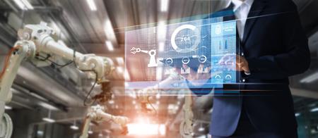 Menadżer Inżynier przemysłowy za pomocą maszyny do sprawdzania i sterowania automatyki ramion robotów w inteligentnej fabryce przemysłowej na ekranie wirtualnego interfejsu, koncepcja Przemysłu 4.0 Zdjęcie Seryjne