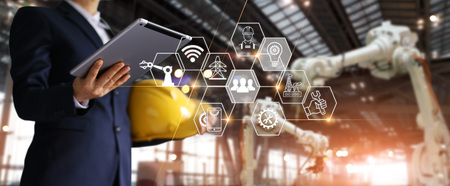 Un arquitecto futurista, empresario, gerente de ingeniería con tableta con red de iconos, robótica industrial, máquina de brazos de robot de automatización en un sitio de construcción inteligente. Concepto de tecnología de la construcción Foto de archivo
