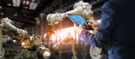 Manager des Wirtschaftsingenieurs, der die Roboterarmmaschine des Tablettprüf- und Steuerautomaten in der intelligenten Fabrikindustriesoftware auf Überwachungssystem verwendet. Schweißroboter und digitaler Fertigungsbetrieb. Industrie 4.0-Konzept