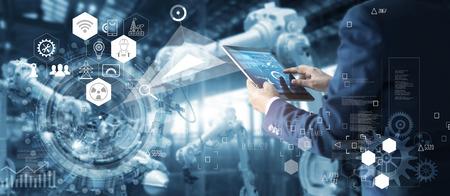 Manager Technicial Industrial Engineer arbeitet und steuert Roboter mit Überwachungssystemsoftware und Icon Industry-Netzwerkverbindung auf dem Tablet. KI, künstliche Intelligenz, Automatisierungsroboterarmmaschine in der intelligenten Fabrik auf blauem digitalem Hintergrund, innovative und futuristische Technologie.