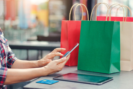 Online shopping. Woman using smartphone with credit card. Mobile phone, Website on ipad and shopping bags on table, department store background. Consumer commerce concept. Imagens