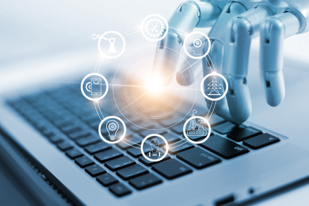 Hand of robotics connecting to industrial network connection on laptop. Artificial intelligence. Futuristic technology and manufacturing concept.