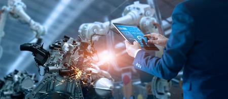 El ingeniero gerente verifica y controla la máquina de brazos de robot de automatización en una fábrica inteligente industrial en el software del sistema de monitoreo en tiempo real. Robótica de soldadura y operación de fabricación digital. Foto de archivo