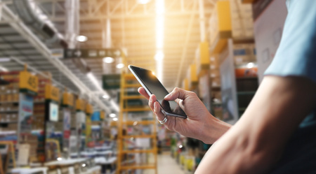 Factory worker using application on mobile smartphone to operrate automation for modern trade. Checking order in large warehouse. Import and export the shipping cargo.