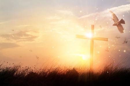 Silhouet christelijk kruis op gras bij zonsopgang achtergrond met wonder heldere verlichting, religie en aanbidding concept Stockfoto