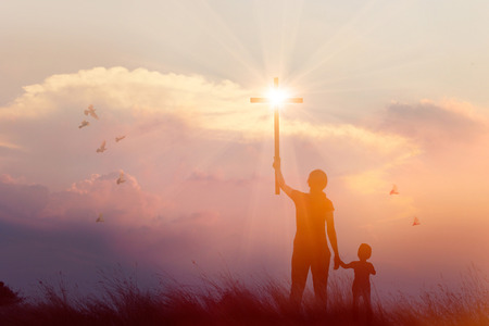 Silhouette of mother and son christian prayers raising cross while praying to the Jesus on sunset background, worship concept Banco de Imagens