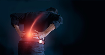 Mann leidet unter Rückenschmerzen Ursache des Office-Syndroms, seine Hände berühren den unteren Rücken. Medizin- und Gesundheitskonzept Standard-Bild